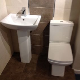 Newly installed toilet and sink in a home by our team in Derby